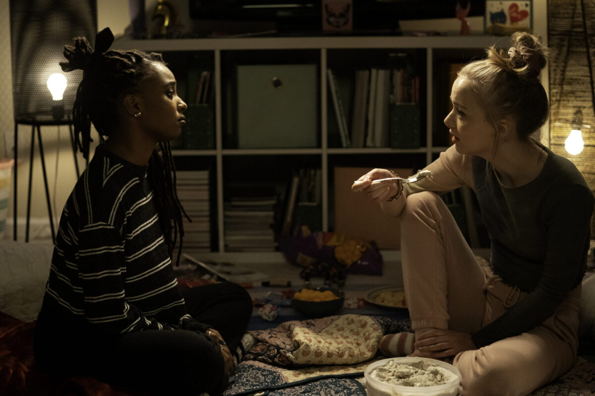 Two young women, one Black and one White, sitting on the floor face to face, serious looks on their faces.